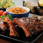 Racks of barbecue ribs drenched in sauce wiht salad and cornbread